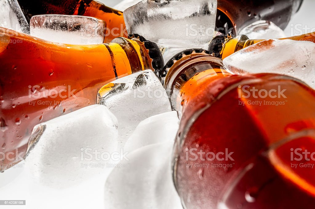 Soda glass bottles in a refrigerated ice cubes stock photo