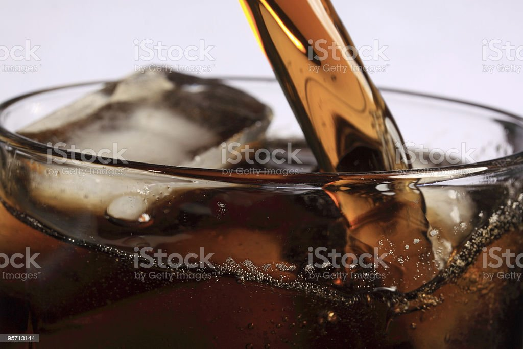 Soda pouring into glass of ice stock photo