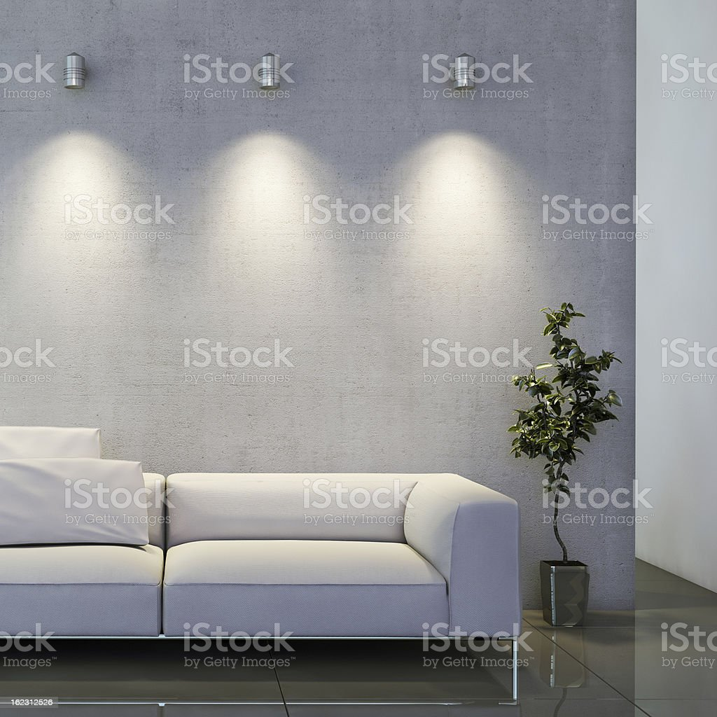 Sofa and a plant in front of well lit wall royalty-free stock photo