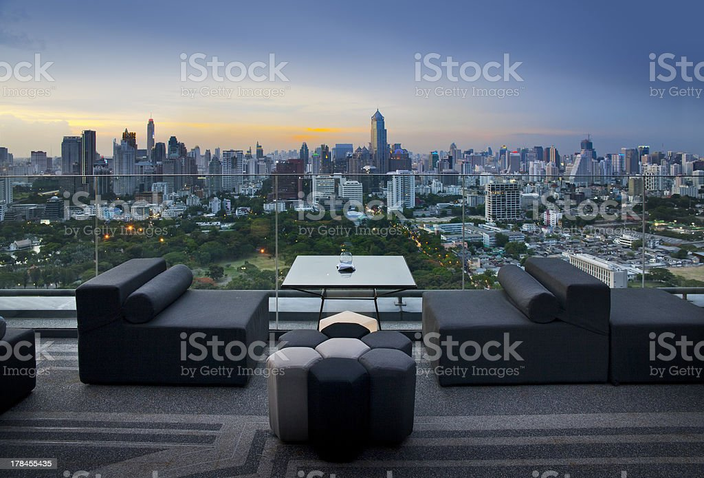 Sofa on terrace overlooking green park and building, Bangkok, Thailand stock photo