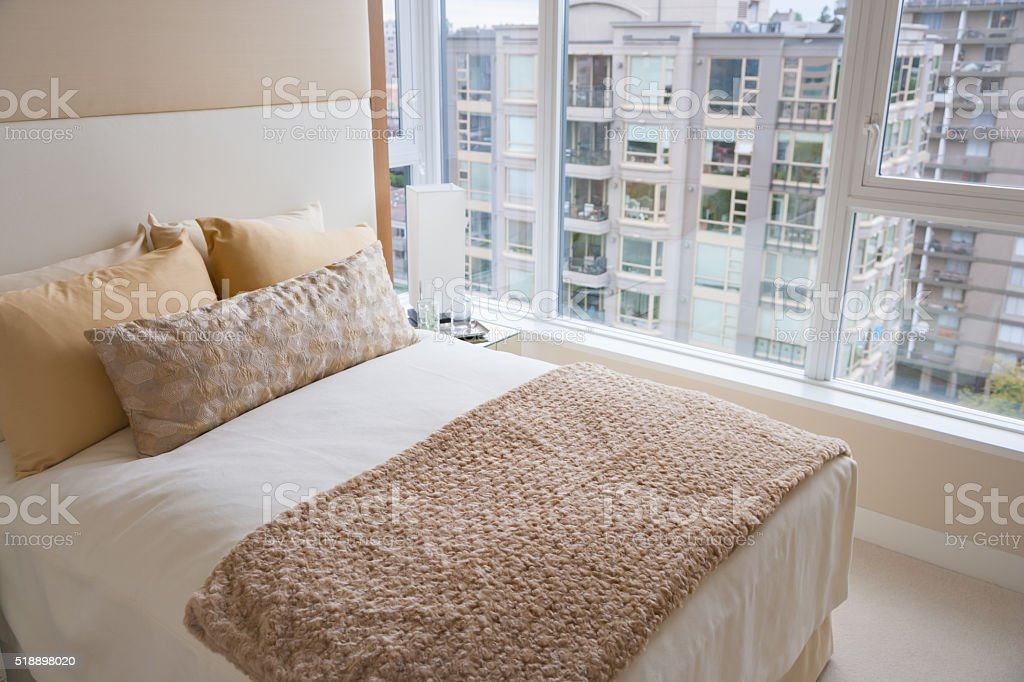 Soft bed beside large windows in bedroom stock photo