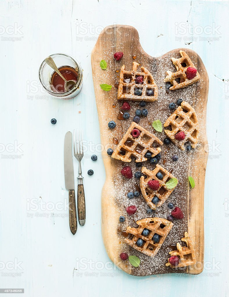 Soft Belgian waffles with berries, honey and mint on rustic stock photo