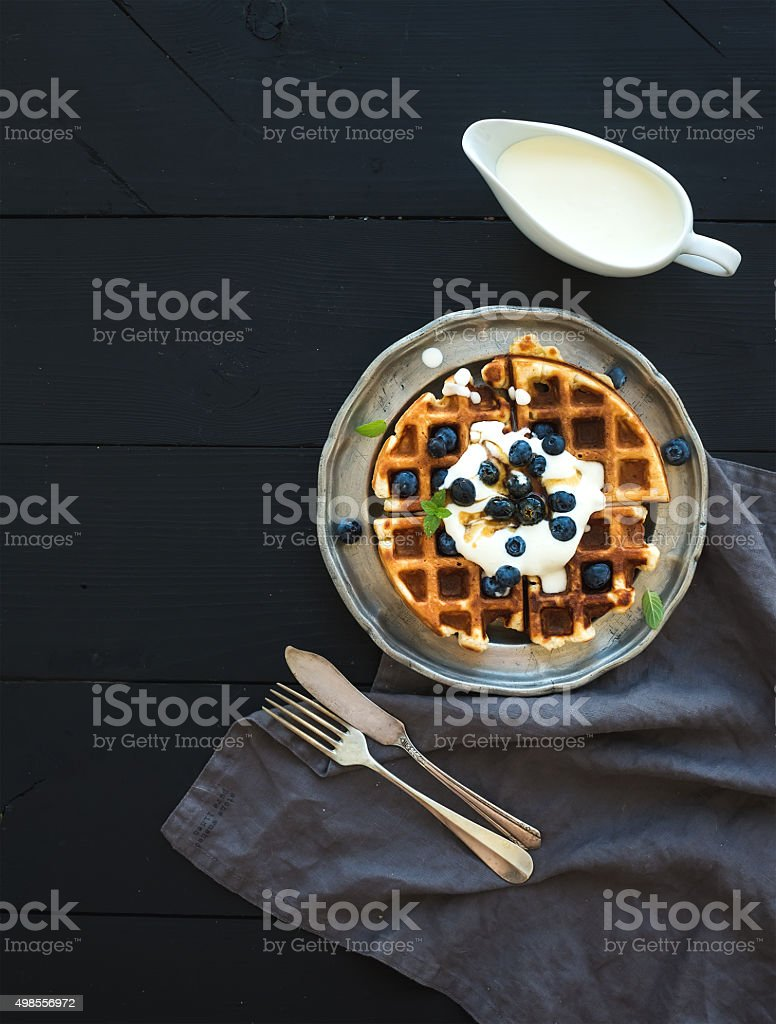 Soft Belgian waffles with blueberries, honey and whipped cream on stock photo