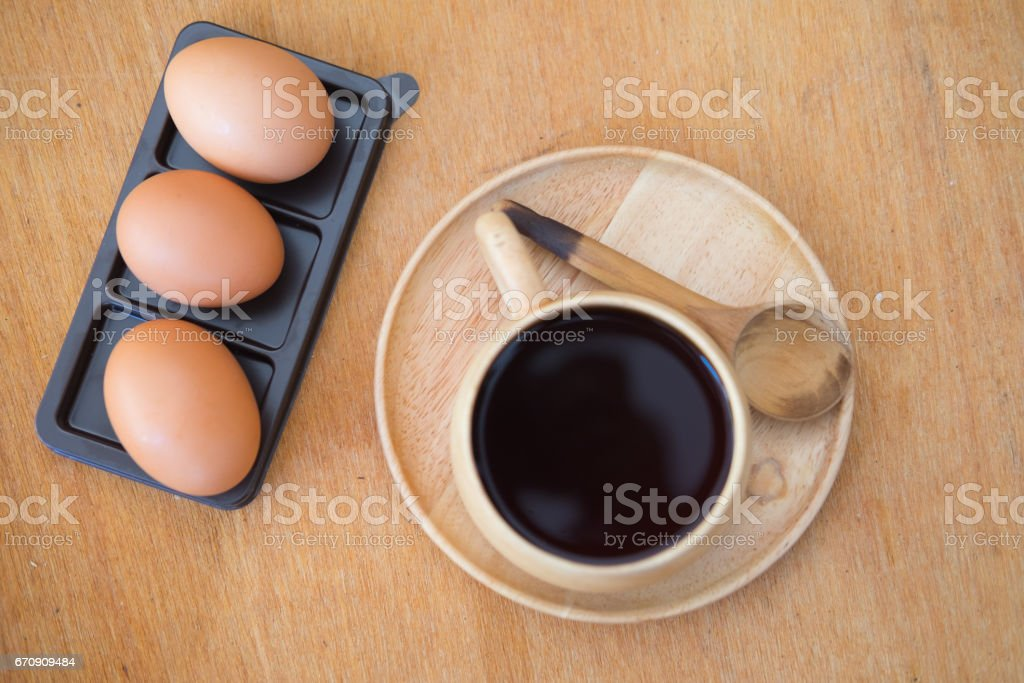 Soft boiled egg and coffee on wood table stock photo