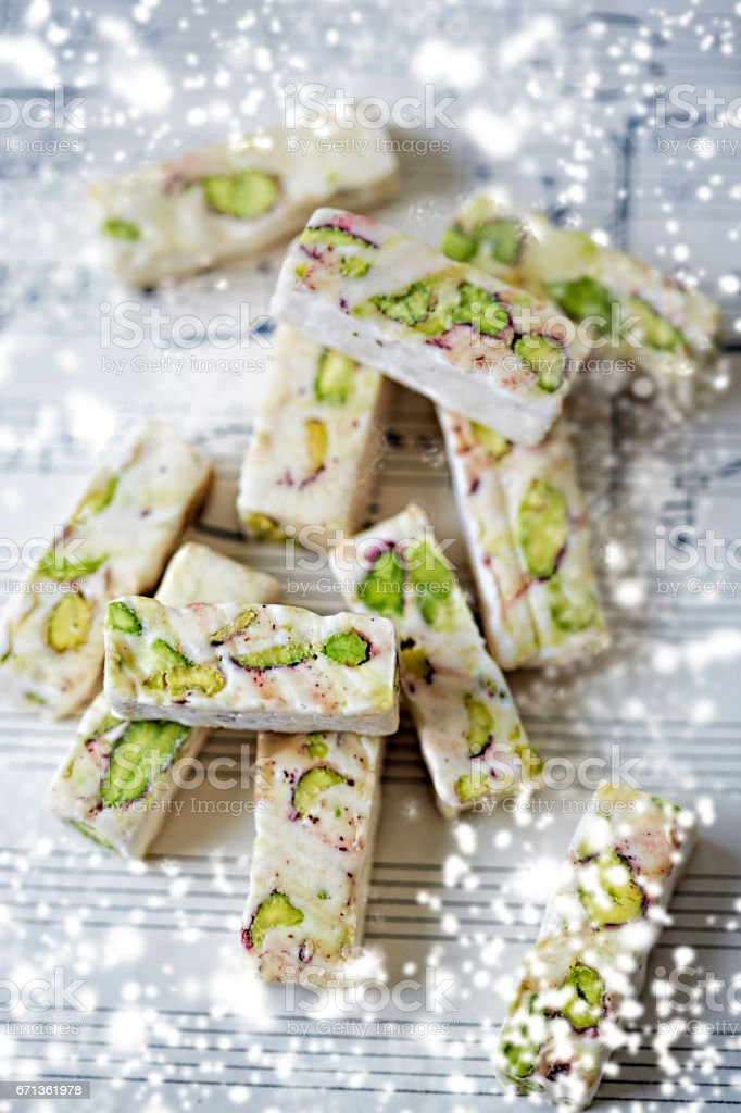 Soft cubes of white nougat with pistachios stock photo