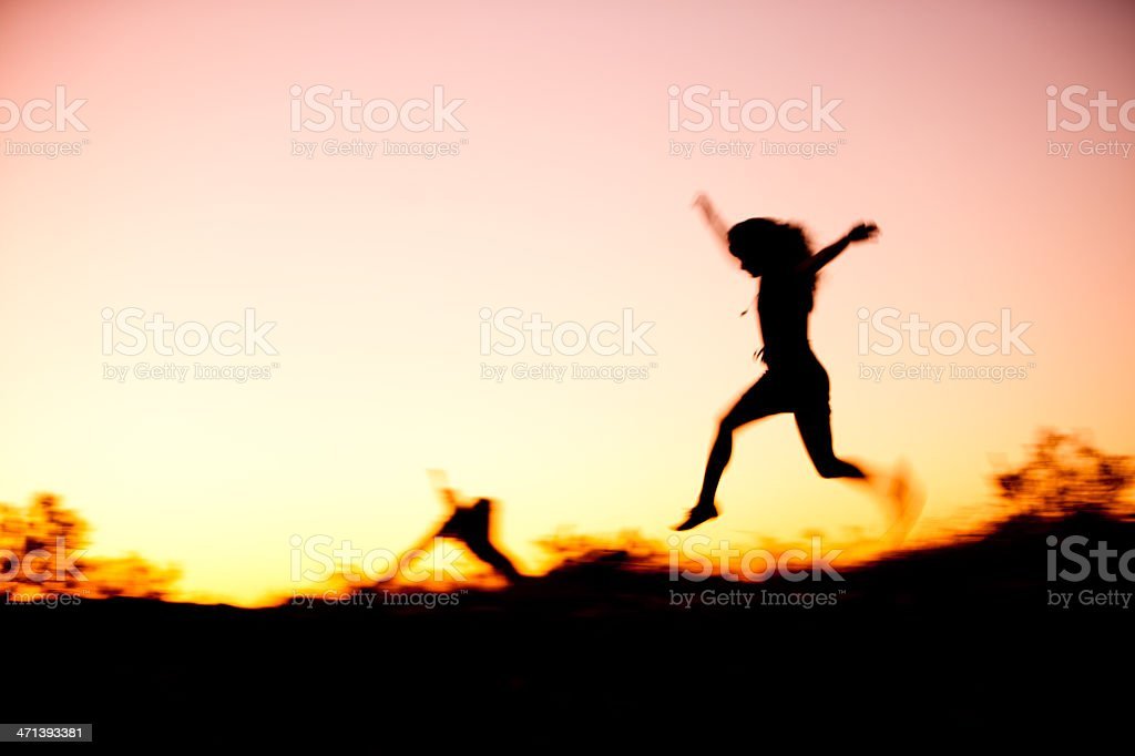 Soft dreamy image of woman leaping at sunset stock photo