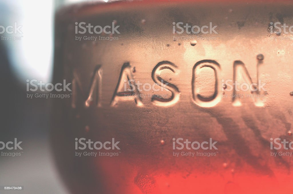 Soft peachy-pink to red mason jar background. stock photo