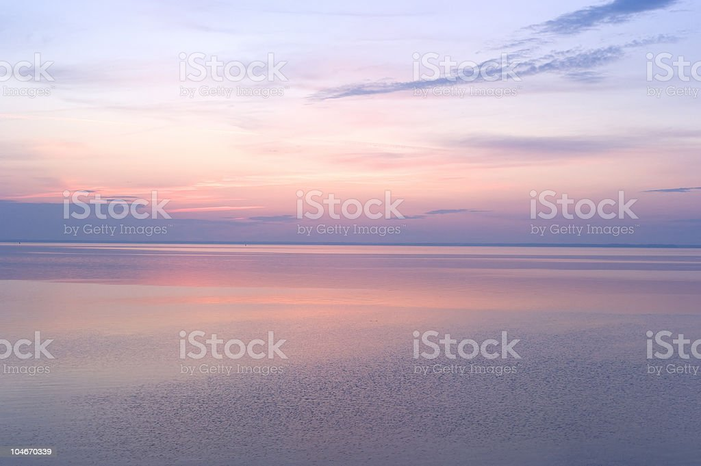 Soft pink and purple sunrise over calm waters royalty-free stock photo