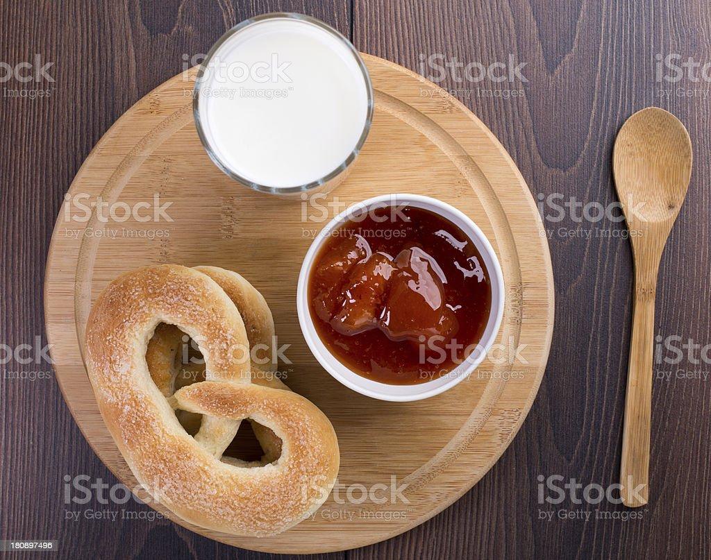 Soft pretzels, apricot jam and glass of milk stock photo