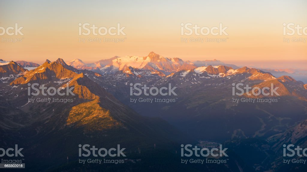 soft sunlight over rocky mountain peaks, ridges and valleys of the Alps at sunrise stock photo