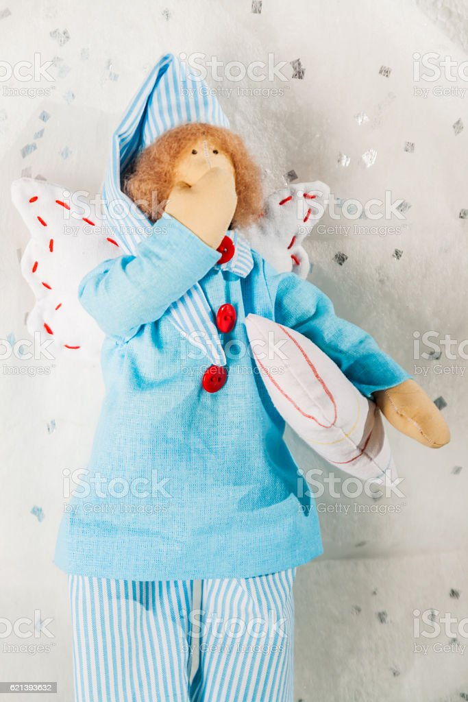Soft textile doll in blue pajamas and a pillow stock photo