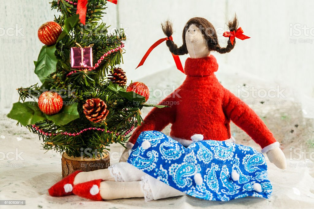 Soft textile doll near a Christmas tree with gifts stock photo