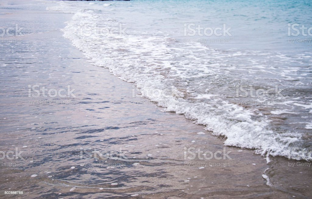 Soft wave of blue ocean on a sandy beach. With the blur. Toning. stock photo