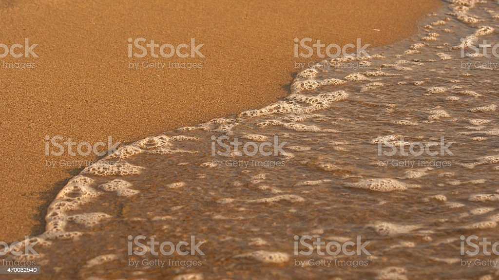 Soft wave of the sea on the sunny beach stock photo