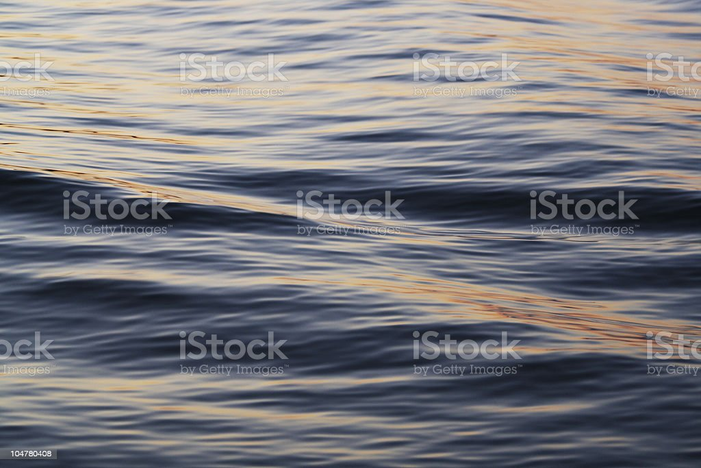 Soft waves with reflections of the sun going down royalty-free stock photo