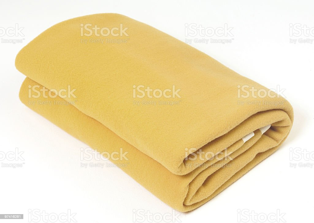 A soft yellow blanket folded up on a white background royalty-free stock photo