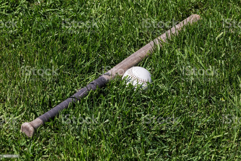 An old taped up wooden softball bat and softball in the green grass.