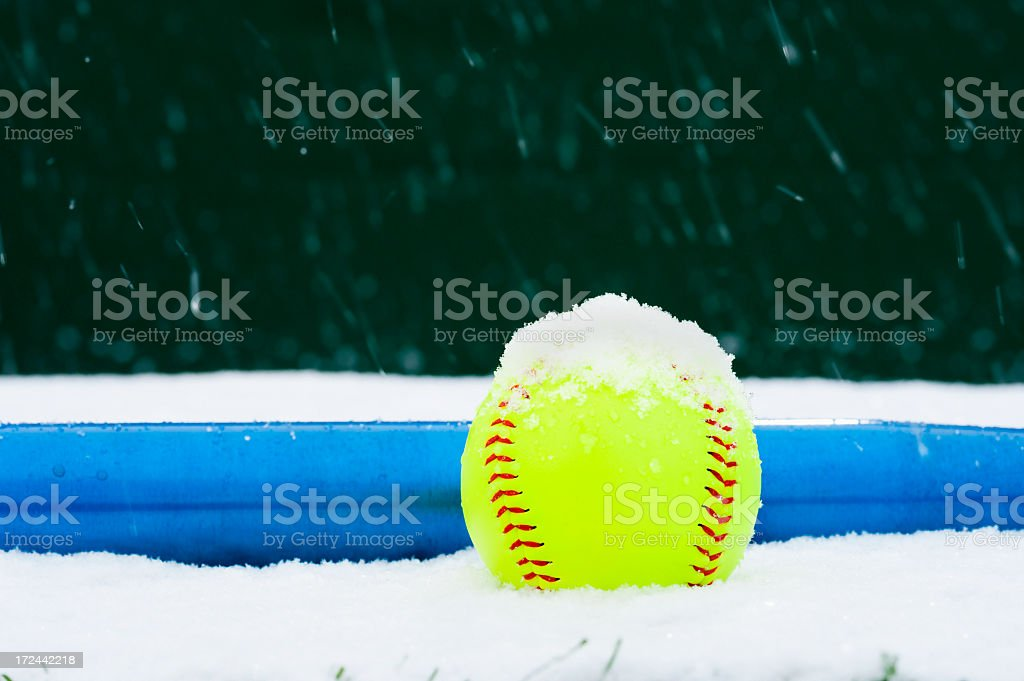 A Fluorescent Softball and Blue Aluminum Bat sitting on a snow...