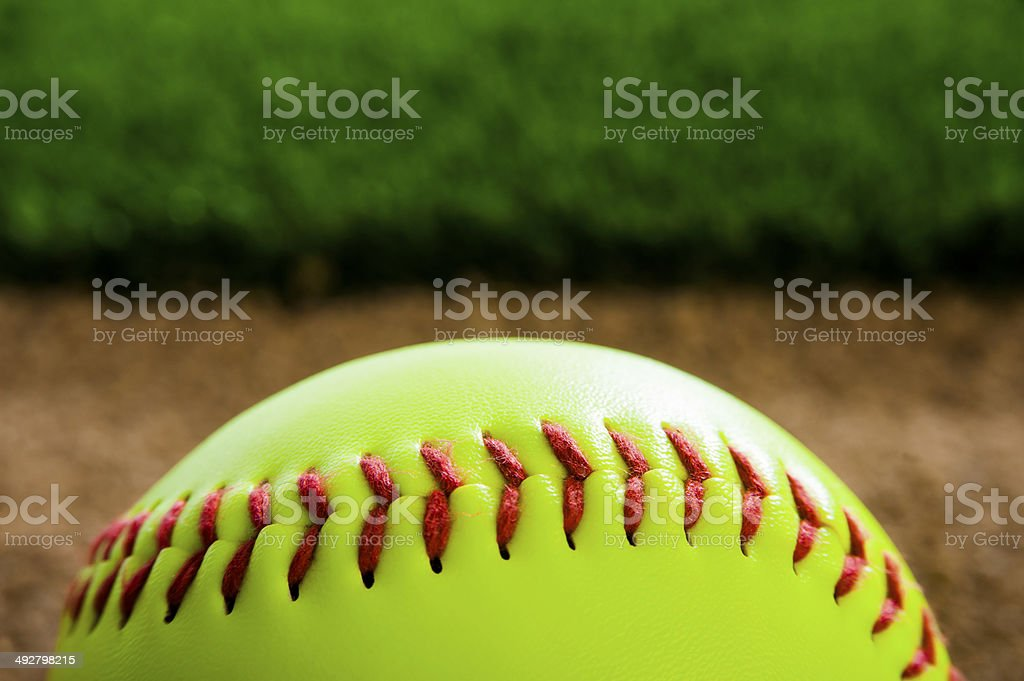 A Close-up of a New Softball in the dirt next to grass