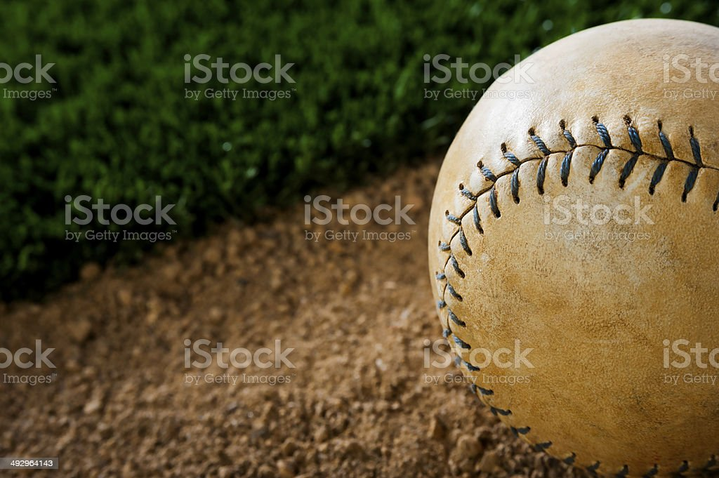 A Close-up of an Old Worn Softball in the dirt next to grass