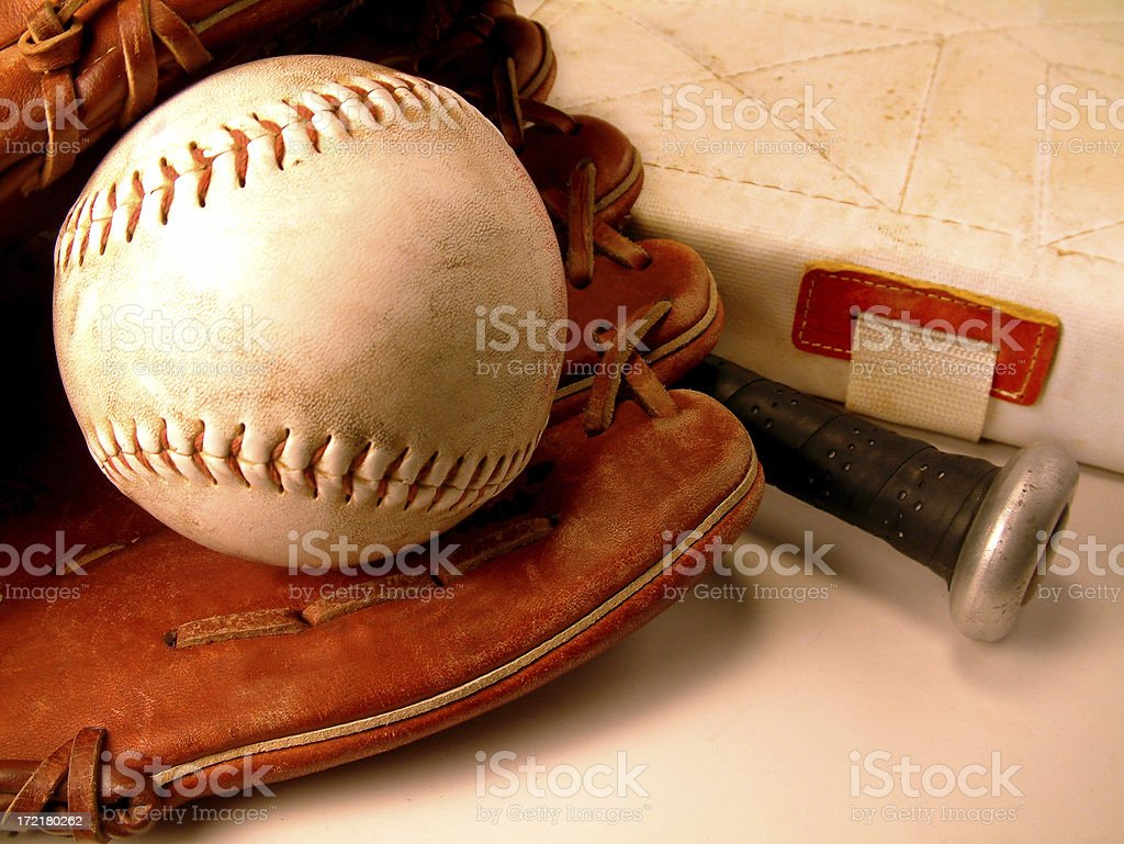 \'Close-up still life of a softball with glove, bat and base.\'