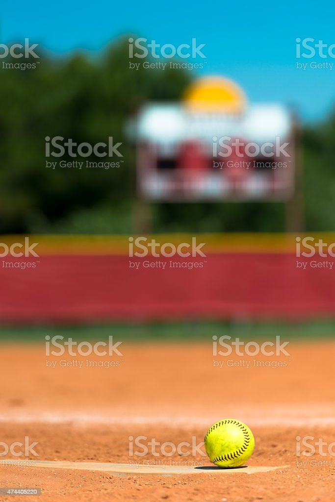 Softball on pitchers mound with scoreboard in background