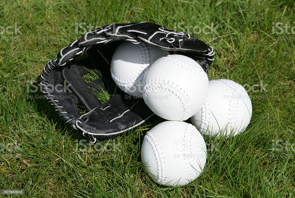 softball glove and balls on grass