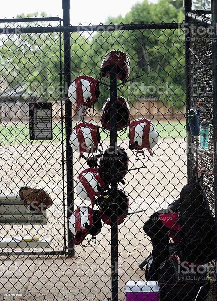softball helmets hanging on rack in dug out royalty-free stock photo