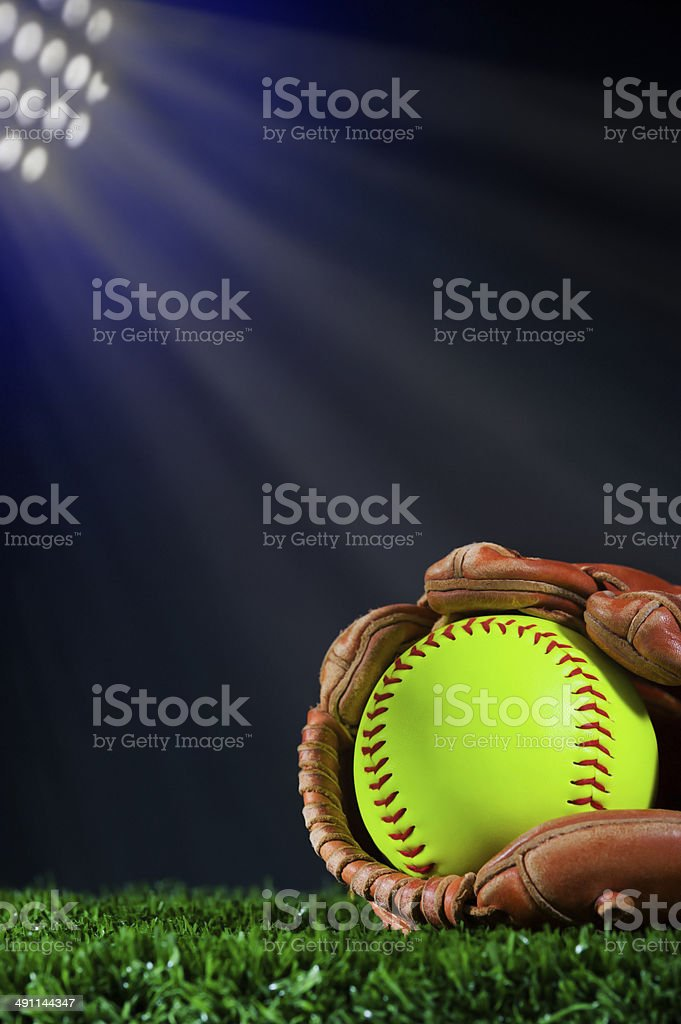 Softball in glove on grass under the lights Night Game stock photo