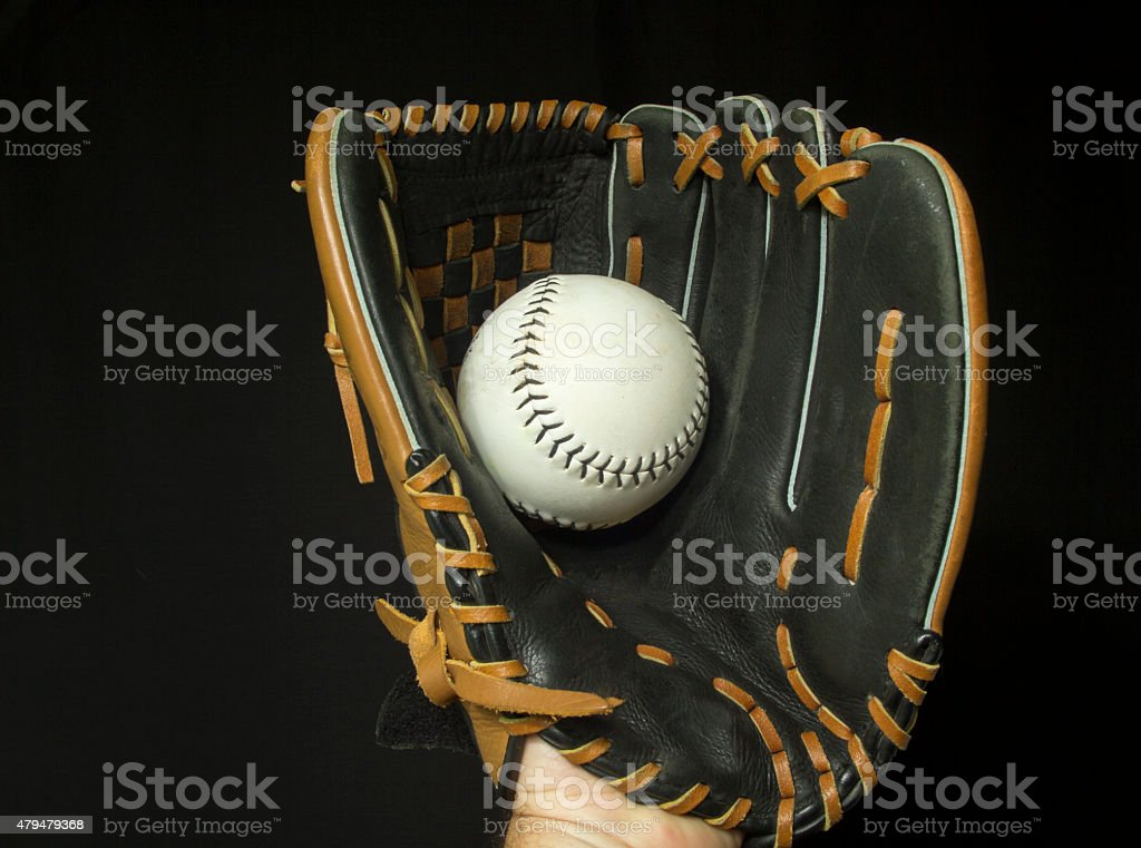 Softball mitt with white softball in webbing.
