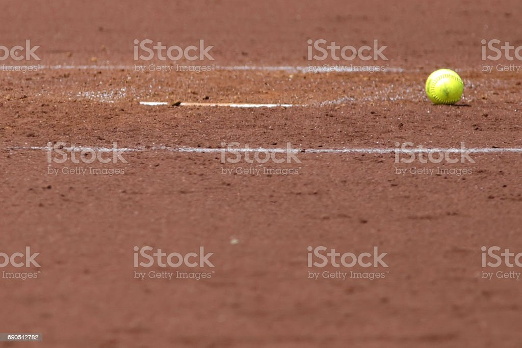 A softball lies on the sandy soil of the infield.