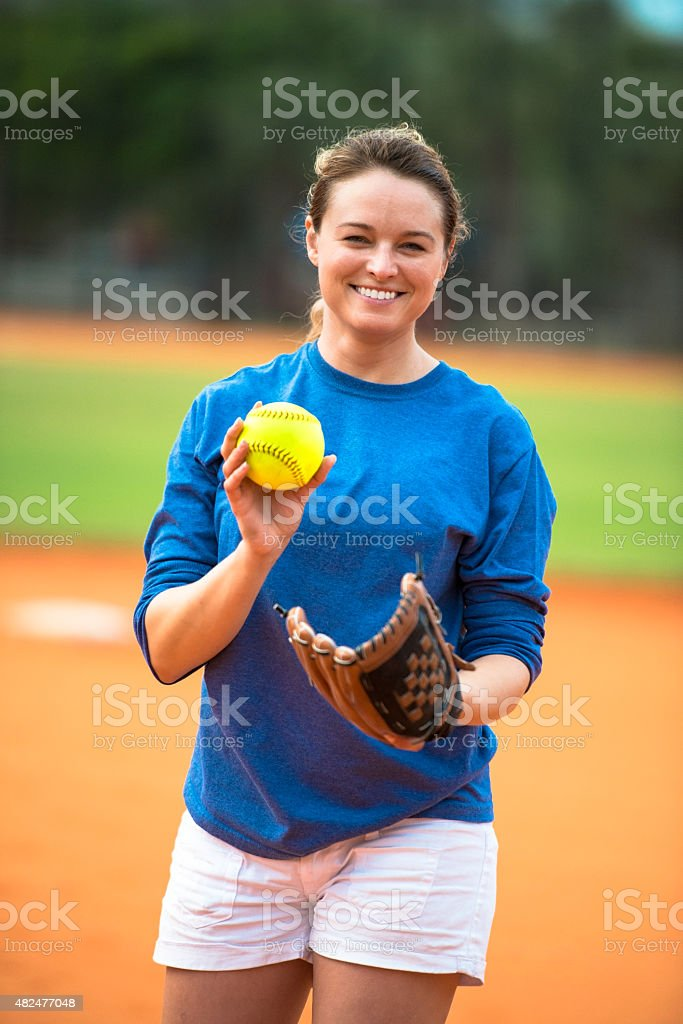Young woman softball pitcher on baseball field