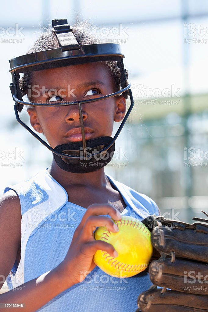 African American girl playing softball, wearing face mask .