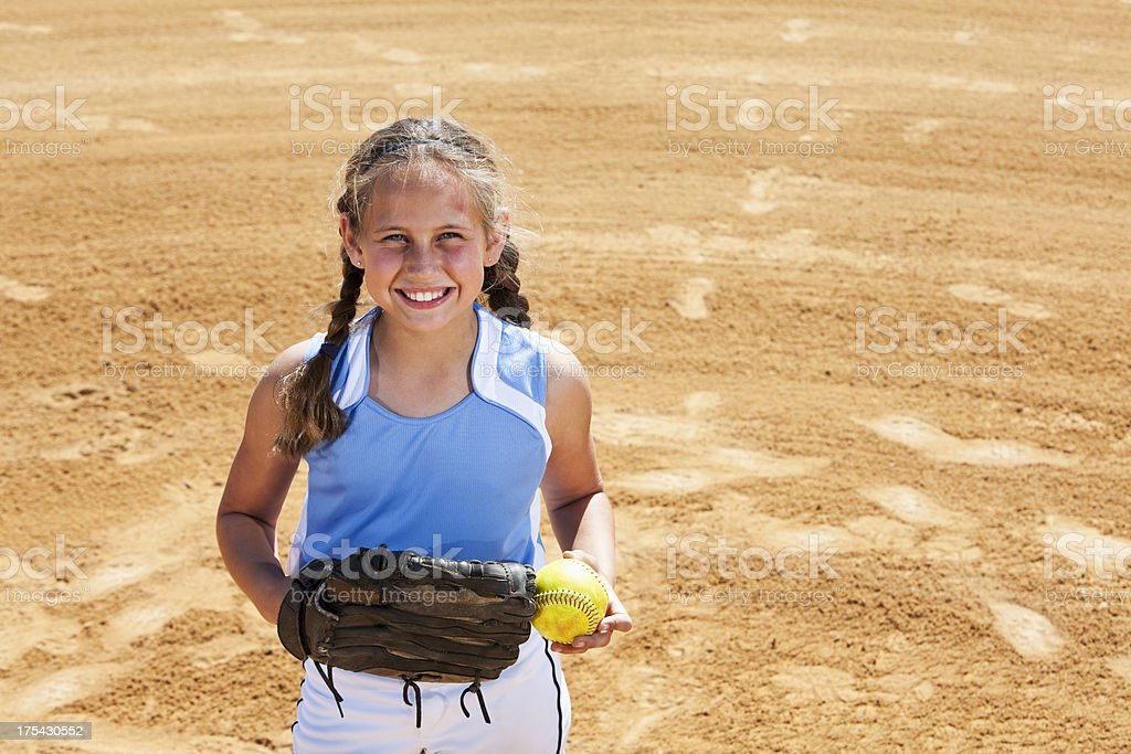 Girl playing softball, standing on pitcher\'s mound.