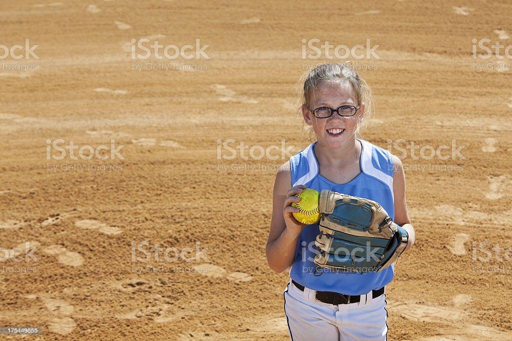 Girl playing softball, standing on pitcher\'s mound.