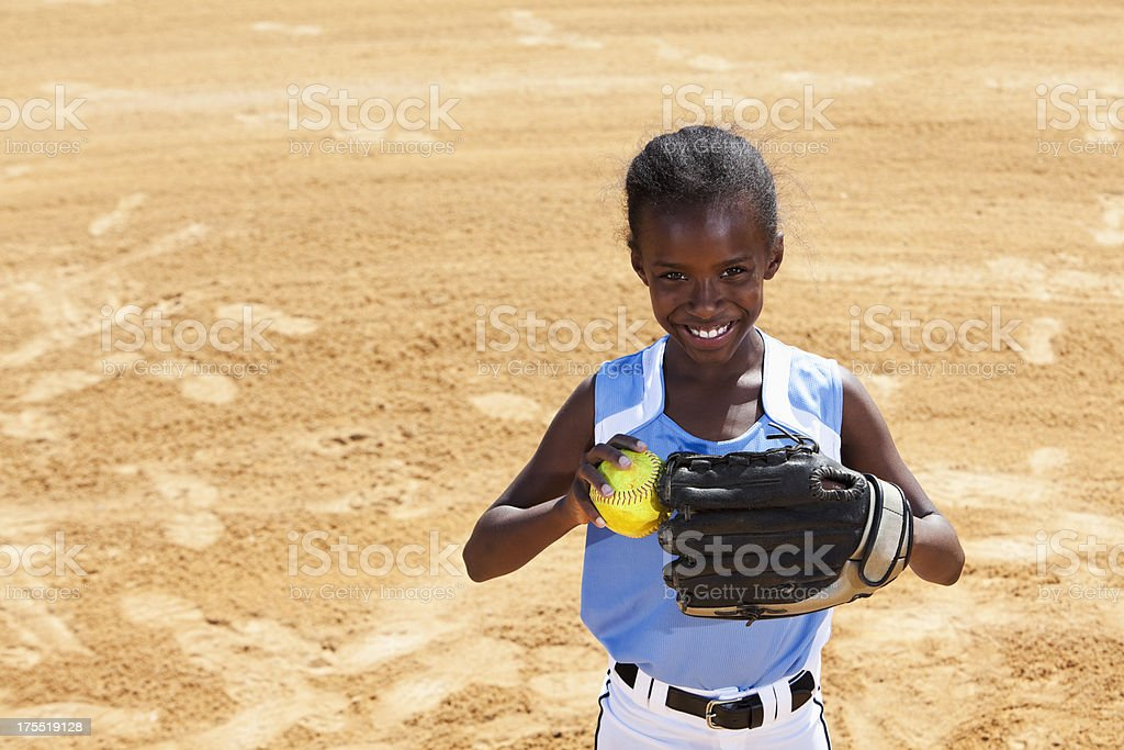 African American girl playing softball, standing on pitcher\'s mound.