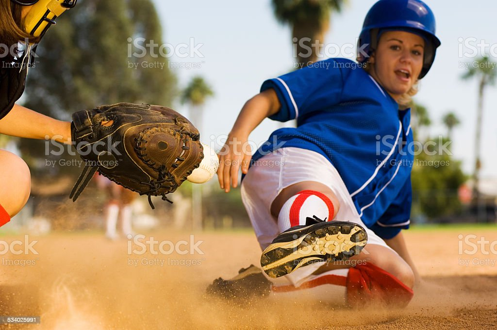 Softball Player Sliding Into Home Plate stock photo