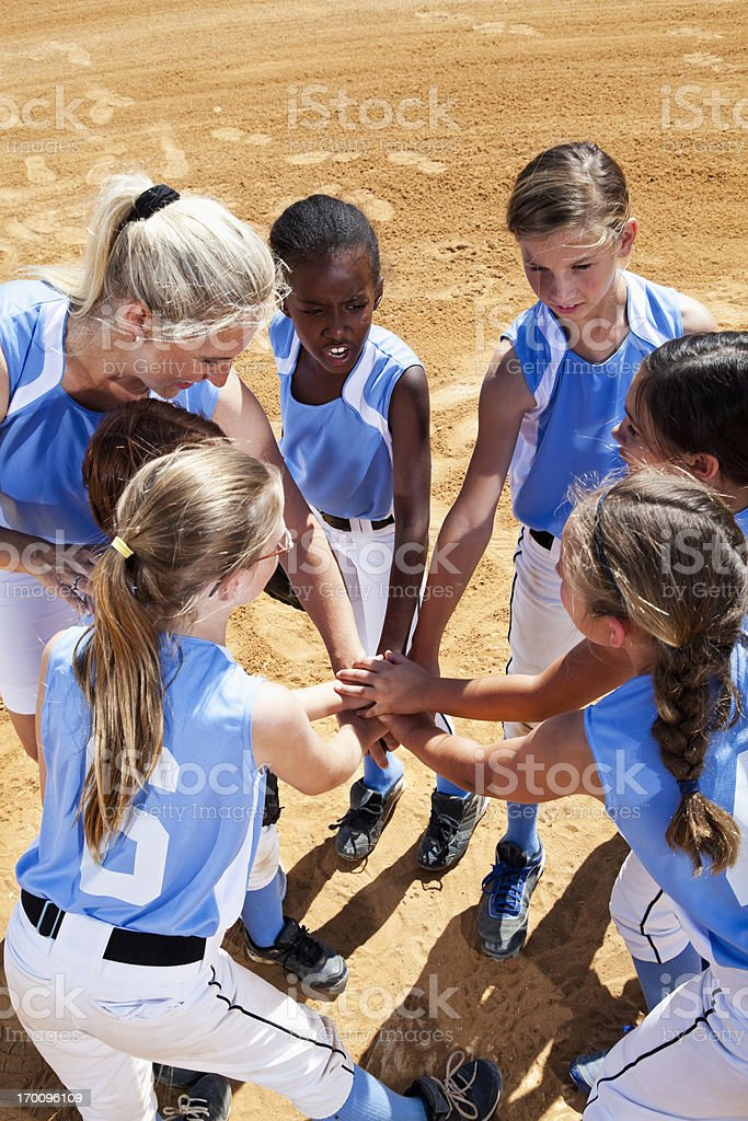 Softball players with coach in huddle doing team cheer royalty-free stock photo