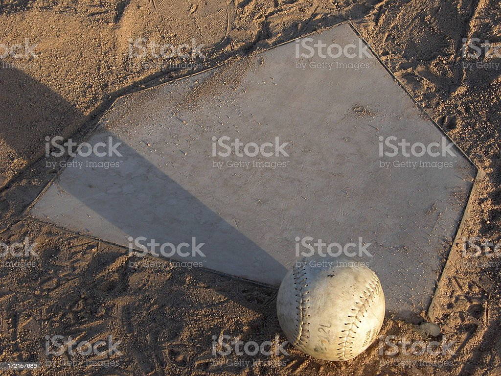 Softball Resting on Home Plate stock photo