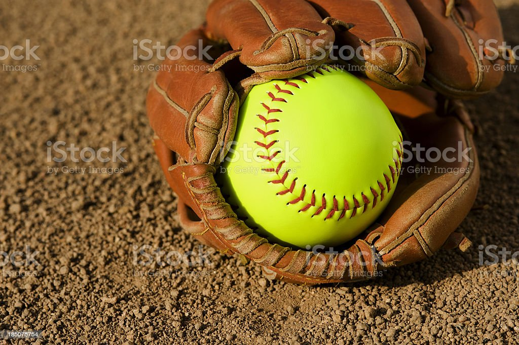 A softball rests inside of a glove sitting in the dirt stock photo