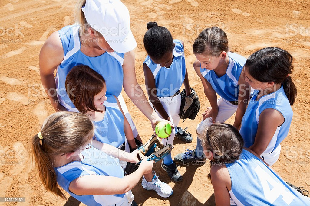 Softball team with coach in huddle stock photo