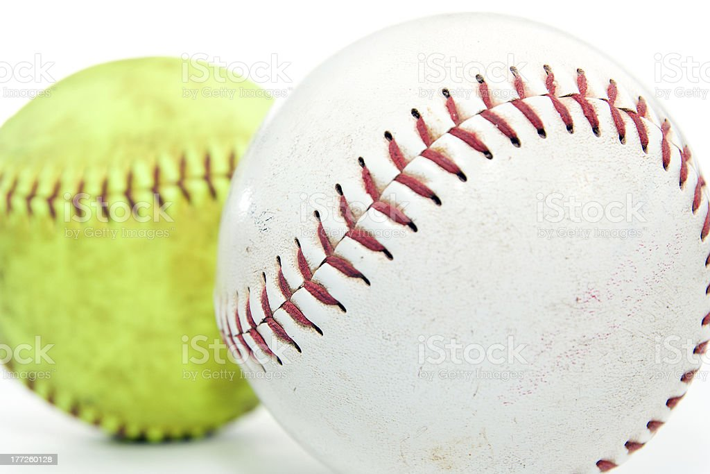 \'Two regulation sized softballs, one white and one yellow on white...
