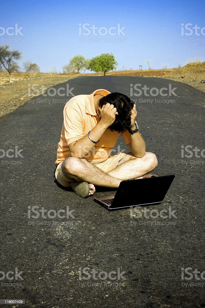 Software professional sitting using laptop in the middle of road royalty-free stock photo