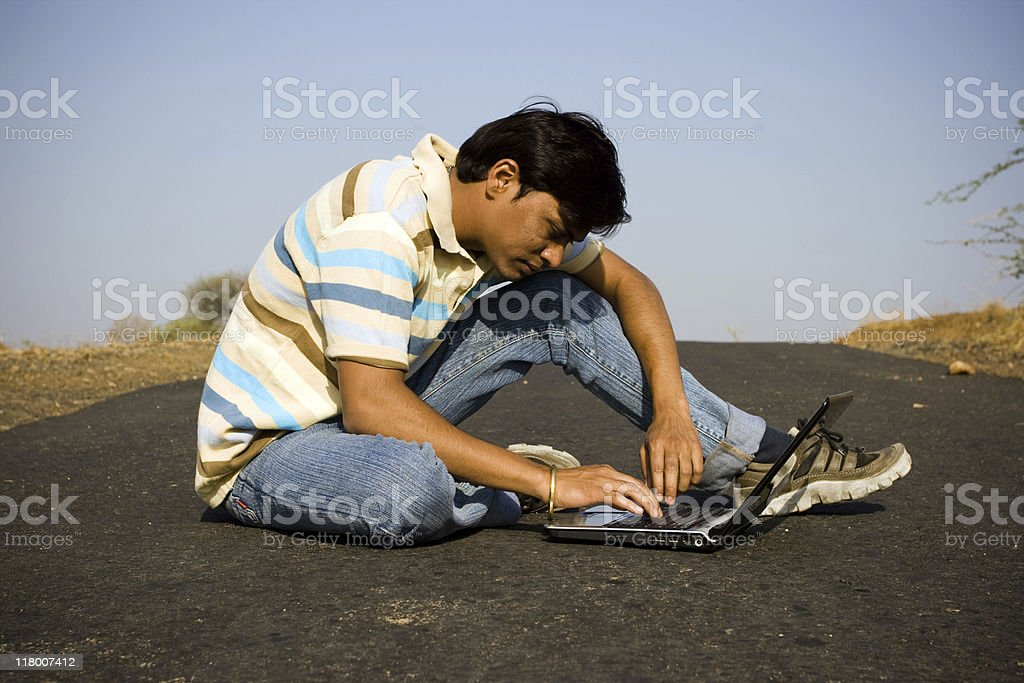 Software professional sitting using laptop in the middle of road stock photo