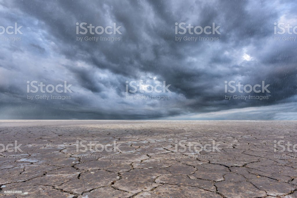 Soil drought cracked landscape and storm clouds background stock photo
