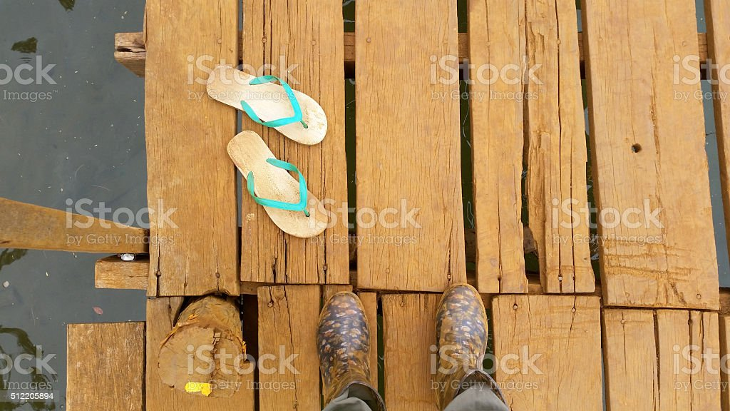 Soiled Boots and slippers on a jetty stock photo
