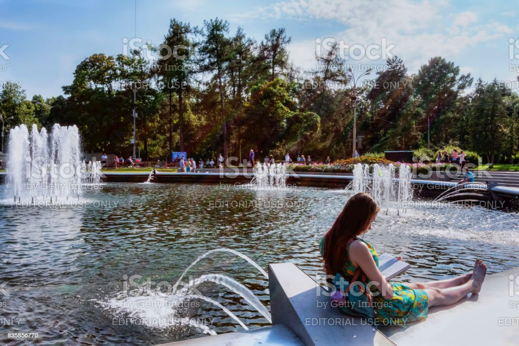 Sokolniki Park woman reads book on the edge of the fountain, she enjoys the summer day of  Mariners of the Navy army stock photo