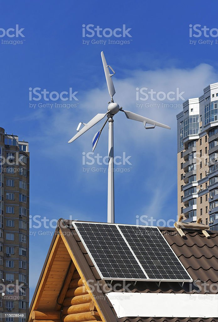 Solar and wind energy generators on wooden house. royalty-free stock photo