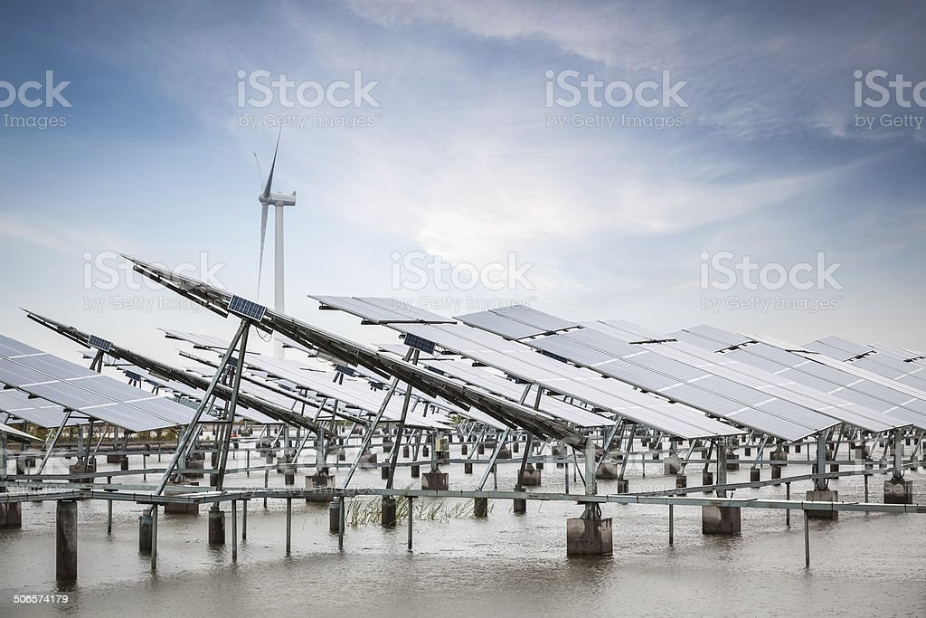solar and wind power in coastal mud flat stock photo