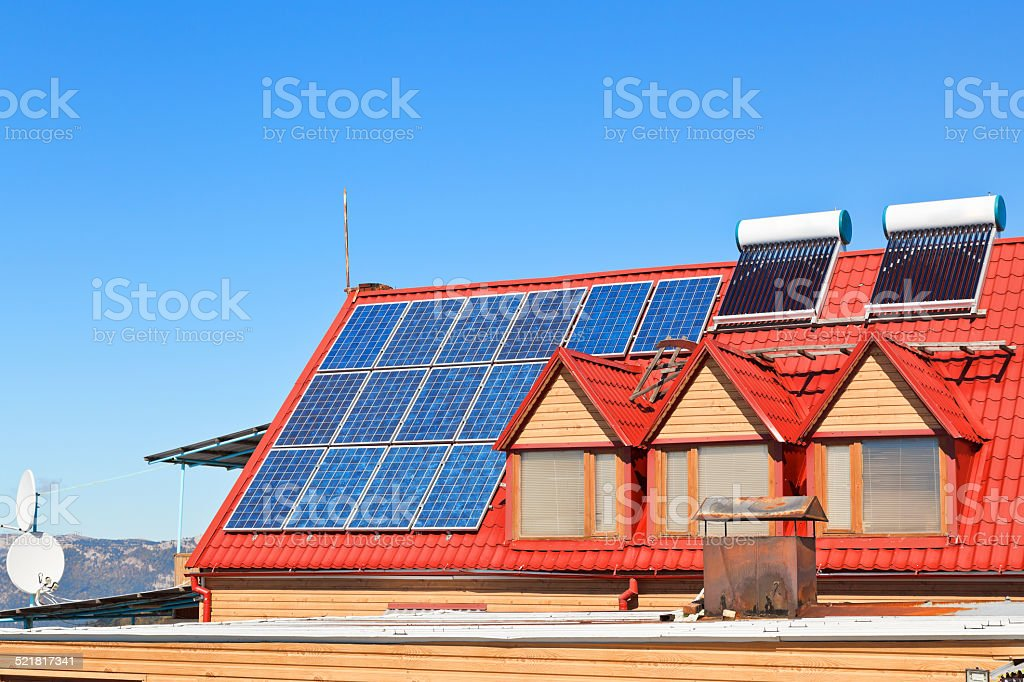 Solar Batteries and heaters on house roof stock photo